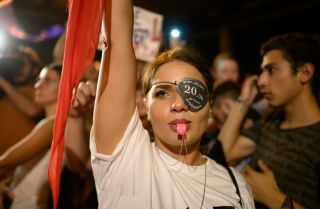 A woman raises her flag and blows a whistle at Georgia's Parliament building. She wears an eye patch to protest the dispersal of a previous demonstration.