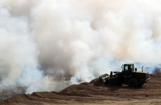 Iraqi forces attempt to extinguish a blaze set by the Islamic State in October 2016 south of Mosul.