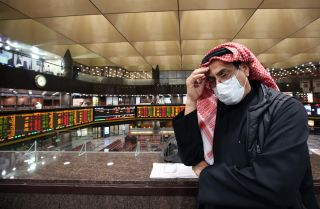 A trader wearing a protective mask stands on the floor of the Boursa Kuwait stock exchange in Kuwait City, Kuwait, on March 1, 2020.