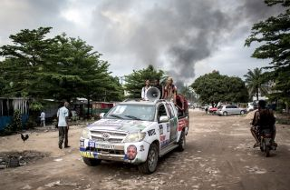 A campaign car is seen as smoke rises from a fire at the independent Congolese electoral commission's warehouse in Kinshasa on Dec. 13, 2018, 10 days ahead of presidential elections that have been foreshadowed by violence.
