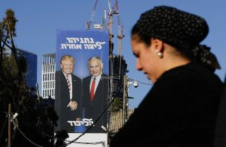 "An election billboard in Tel Aviv on Feb. 3, 2019, shows Israeli Prime Minister Benjamin Netanyahu and U.S. President Donald Trump shaking hands. The Hebrew writing reads, ""Netanyahu, in another league."""
