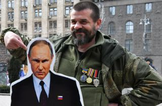 A Ukrainian veteran poses with a cardboard cutout of Russian President Vladimir Putin during a March 29, 2019, rally in Kiev against Russia and pro-Russian candidates running in the country's March 31 presidential election.