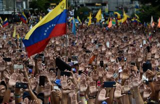 Protesters raise their hands during a rally against Venezuelan President Nicolas Maduro in Caracas on Jan. 23, 2019.