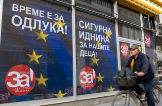 A man rides his bicycle past campaign posters reading 'For a European Macedonia' in Skopje on Sept. 29, 2018. Macedonia is holding a referendum on Sept. 30 on whether to change the country's name.
