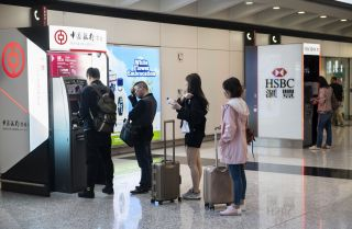 Travelers are seen withdrawing cash at the Bank of China and HSBC ATM at Hong Kong international airport.