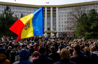 People gather outside the Moldovan parliament during a rally by the pro-European opposition ACUM bloc to protest against parliamentary election results from February.