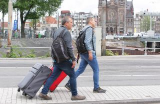 Two tourists pull their bags on the street in 2019 in Amsterdam, Netherlands.