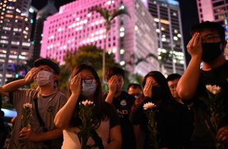 Protesters cover their right eyes as they attend the Stand in Silence for the 74th Anniversary of the Liberation of Hong Kong event at the cenotaph in Hong Kong on Aug. 30, 2019.