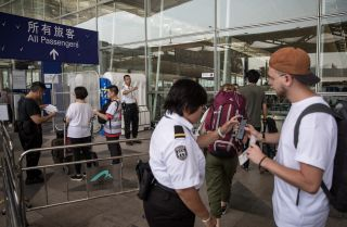 Security staff check passengers boarding passes at the entrance of Hong Kong International Airport.