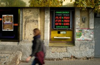 An illuminated sign advertises exchange rates between the hryvnia, the Ukrainian currency, and the U.S. dollar, the Euro and the Russian rouble in Kyiv, Ukraine.