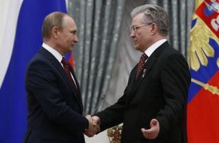 Russian President Vladimir Putin (left) shakes hands with Vladimir Bogdanov, CEO of Surgutneftegas oil and gas company, in Moscow on April 30, 2016.
