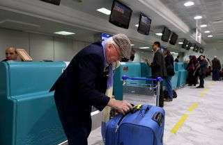 A British traveler packs his phones in his suitcase before boarding his flight for London at Tunis-Carthage International Airport in 2017.