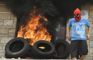 A tire fire burns at the doors to the outer entrance of the U.S. Embassy in Tegucigalpa on May 31, 2019.