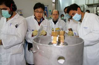 Two inspectors with the International Atomic Energy Agency, second and third from left, observe Iranian technicians stop the production of 20 percent enriched uranium at the Natanz nuclear facility on Jan. 20, 2014.