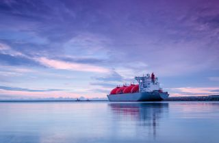 The sun rises over an LNG terminal at sea.