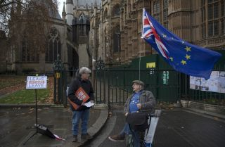 Campaigners on opposite sides of the Brexit issue chat outside the Houses of Parliament on Dec. 5, 2018, in London.