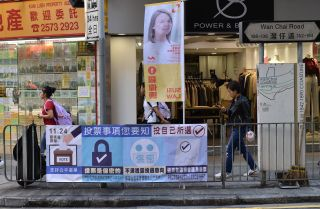 This Nov. 22, 2019, photo shows pedestrians walking past a banner for Hong Kong's district council elections, which are scheduled to take place Nov. 24.