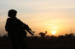 This photo shows the outline of a soldier standing guard at sunset in Niamey, Niger, on Dec. 22, 2019.