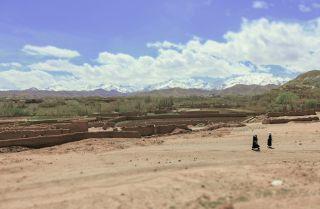 Villagers walk across a striking Afghan rural landscape.