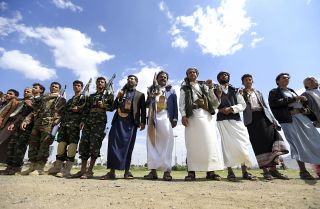 Armed men gather to protest against the Saudi-led intervention in Yemen.