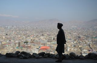 An Afghan man walks along a hilltop overlooking Kabul on March 21, 2018.