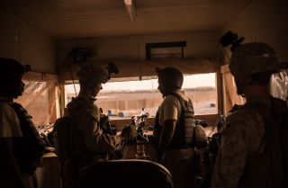 U.S. marines talk to Ugandan contractors at a guard station in Helmand Province, Afghanistan.