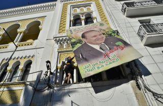 A billboard of Algerian President Abdel Aziz Bouteflika gets taken down in protest of fifth run for the presidency.