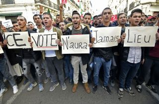 "Algerian demonstrators carry placards reading ""This vote will never take place"" in French in regard to the Dec. 12 presidential election, during a march in Algiers on Dec. 6, 2019."