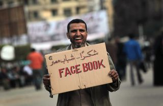An anti-government demonstrator holds a sign during clashes on February 3, 2011 in Cairo, Egypt.
