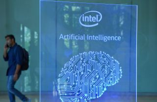 A visitor at Intel's Artificial Intelligence (AI) Day walks past a signboard during the event in the Indian city of Bangalore on April 4, 2017.