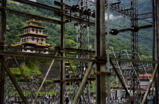A Buddhist temple sits near a hydroelectric grid main in southeastern Bhutan in 2013.
