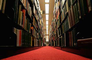 A man walks down a corridor in a library.