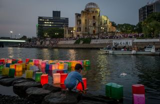 A boy floats a candle lit paper lantern on the river in front of the Atomic Bomb Dome.