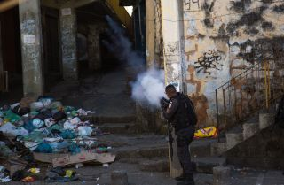 A policeman fires into a building during a protest over the killing of a bystander in Rio de Janeiro during August 2019.