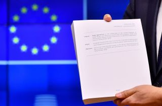 "European Council President Donald Tusk holds the ""draft agreement of the withdrawal of the United Kingdom of Great Britain and Northern Ireland from the European Union"" during a press conference at the European Council in Brussels on Nov. 15."