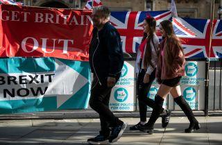 Pedestrians near the British Parliament building pass banners touting Brexit.