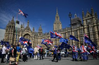 Pro-EU demonstrators hold placards and wave flags as they protest against Brexit, outside of the Houses of Parliament in central London on June 11, 2018.
