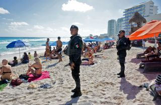 Mexican federal police patrol the beach in Cancun, a resort town rarely touched by violence. But recent drug cartel battle there have resulted in spillover violence that left some tourists dead.