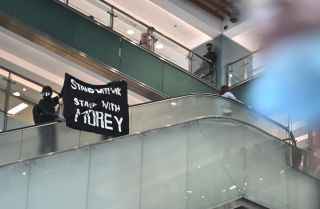 This photo shows a protester in Hong Kong waving a banner of support for NBA team executive Daryl Morey.