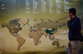 An investor in China examines a map showing investment opportunities in real estate, including in the United States.