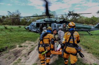 "A Colombian rescue crew evacuates a ""victim"" in a Brazilian air force helicopter during an earthquake simulation exercise conducted by air force members at the Palenquero base in Puerto Salgar, Colombia, on Sept. 6, 2018."