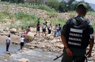 A member of the Venezuelan national guard stands watch at the Tachira River, at the Colombian border. Criminal activity, driven in part by smuggling, will persist in parts of the border region.