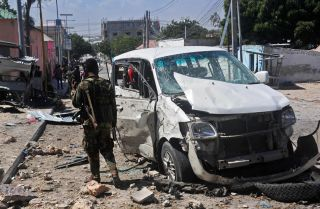 A Somali soldier stands at the scene of a car bomb attack conducted by al Qaeda affiliate al Shabaab near the Peace Hotel in Mogadishu on Jan. 2, 2017.