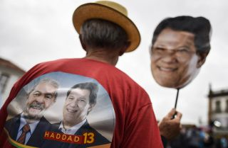 A Workers' Party supporter holds a mask with the face of Brazilian presidential candidate Fernando Haddad on it during a campaign rally in Ouro Preto, Minas Gerais, on Sept. 21 ahead of the Oct. 7 national election.