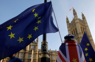 A Brexit opponent displays the Union Jack and the European Union flag outside the Houses of Parliament in London on Dec. 17, 2018.