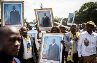 People hold up portraits of the Democratic Republic of the Congo's former president, Joseph Kabila, as they arrive to attend newly elected President Felix Tshisekedi's inauguration on Jan. 24, 2018.