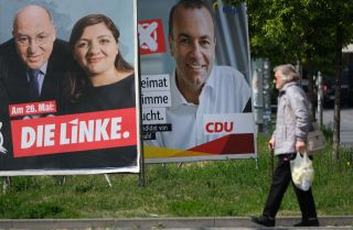 A pedestrian passes election campaign posters of the left-wing Die Linke and of the center-right German Christian Democrats on May 13, 2019, in Berlin.