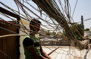 This photo shows an Iraqi man checking a mass of wires connecting homes in Baghdad to electricity.