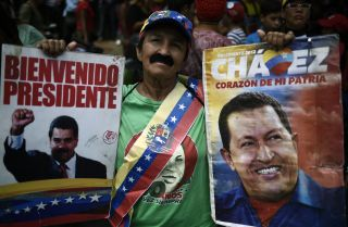 A citizen shows his support for Venezuela's current president, Nicolas Maduro, (pictured in the poster on the left), as well as former President Hugo Chavez.