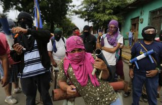 Anti-government demonstrators carry homemade mortars, as they stand near a barricade in Masaya, Nicaragua, on June 5.